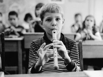 Un niño toca la flauta en clase de música