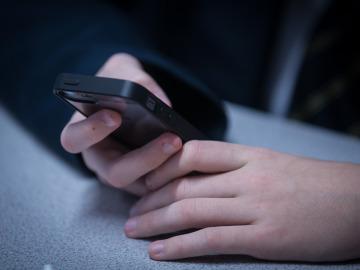 Un niño consulta un teléfono móvil
